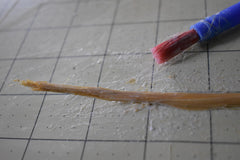 Straw on a grid with a paintbrush