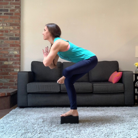 standing figure 4 balance pose with yoga block for stability and strength