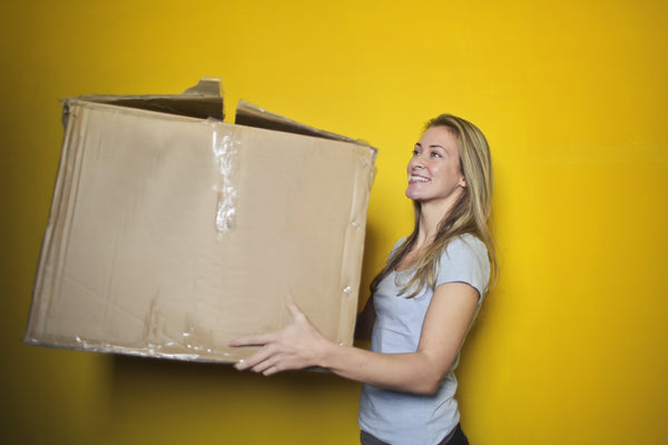 women smiling moving a cardboard box moving house home