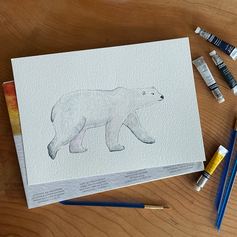 watercolour polar bear with some paints and paintbrushes around