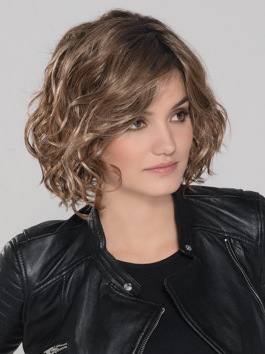 A trendy, mid length style with perfectly placed layers. The monofilament part placement offers the perfect amount of volume
