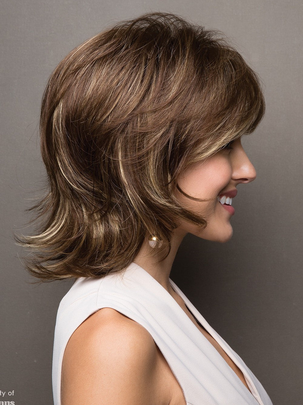 Short, layered cut flips at the collar and has soft, textured edges