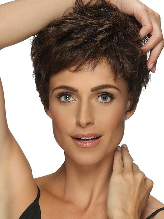 A full-bodied pixie style with curls, wispy bangs & tapered nape