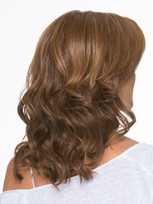 Soft silhouette with beach wave curl texture falls below the shoulders