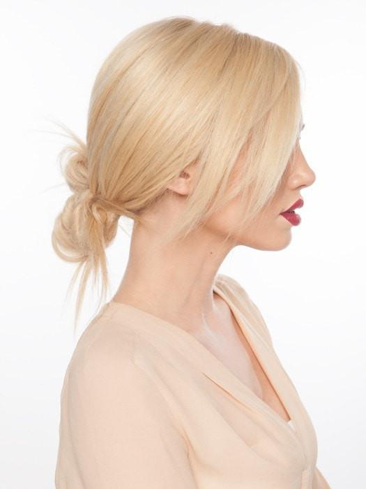 "Styled in a low ""undone"" bun 