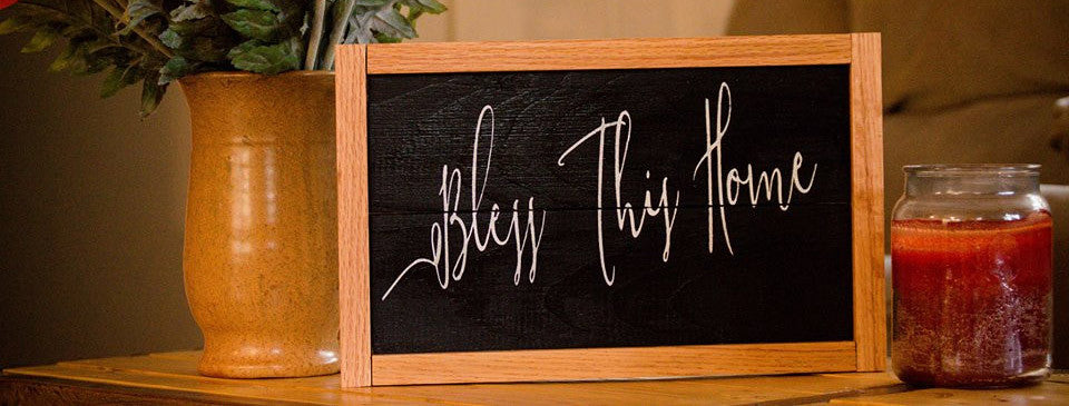 "Rustic black ""Bless This Home"" sign with stained wood frame."