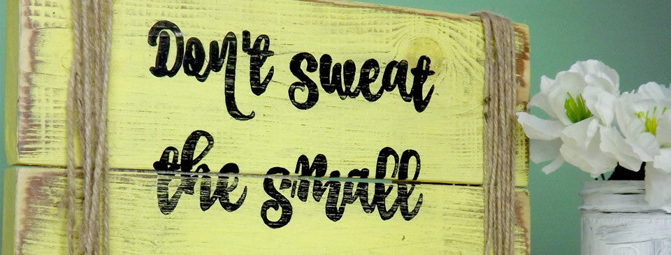 "Rustic yellow ""Dont Sweat The Small Stuff"" wood sign with rope on the sides."