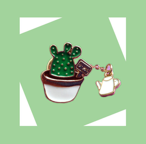 An enamel pin with a cactus in a pot with a watering can dangling charm