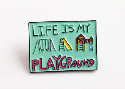 "Teal enamel lapel pin with the words ""Life is My Playground"""
