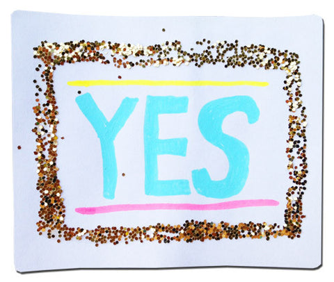 "A handmade sticker with gold glitter & the word ""YES"""