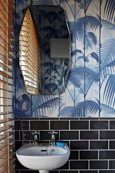 Cole & Son Palm Jungle wallpaper which features layers of blue palm leaves on white background perfect for a bathroom wallpaper