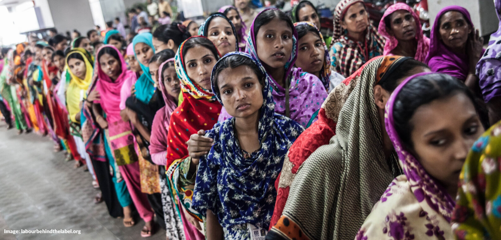 Image: Hundreds of women garment workers stood in a long line looking very solemn.