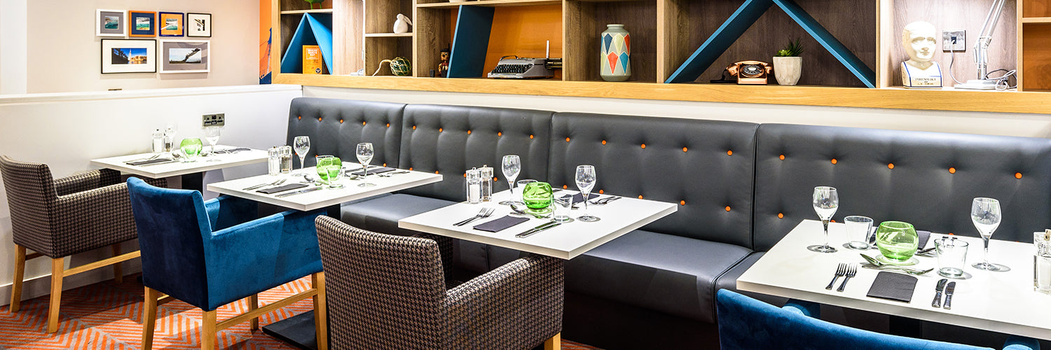 Dark blue fixed restaurant seating with orange button detail