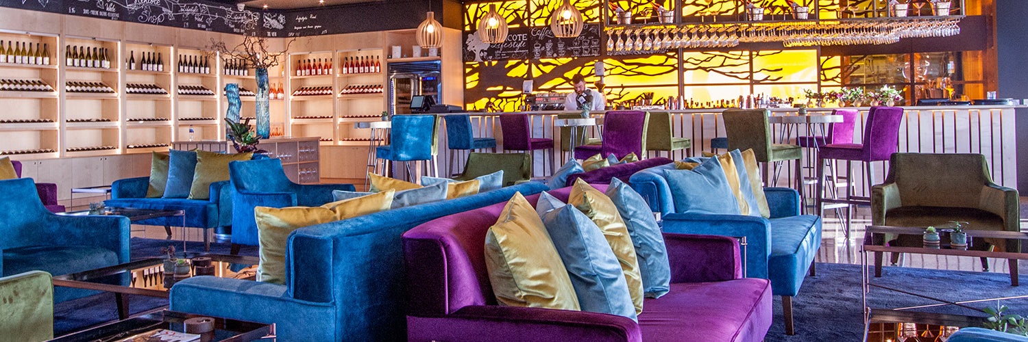 luxury green lounge chairs and purple and blue sofas in bar lounge area