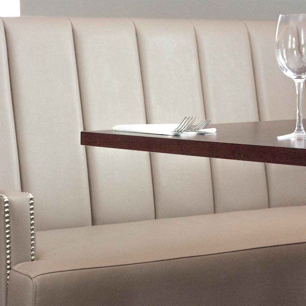 Beige faux leather banquette design with stud detail to arms