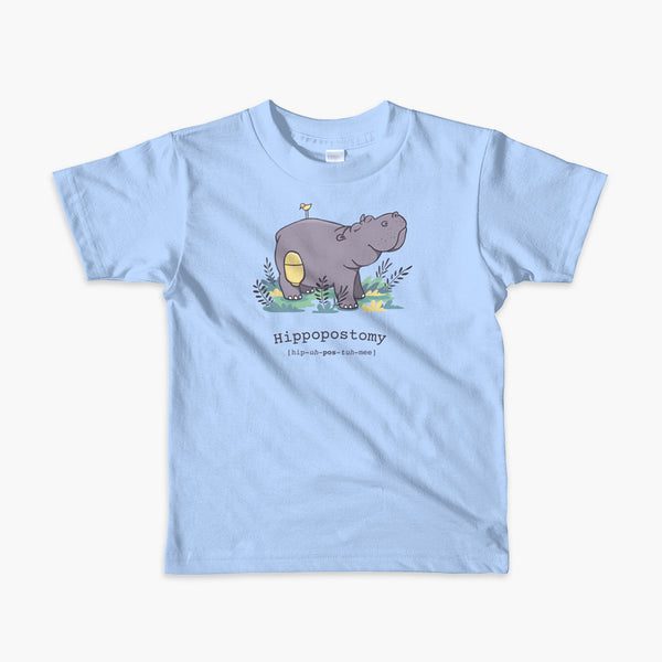 A Hippo or Hippopotamus with an ostomy bag — also known as a Hippopostomy. He is standing in some foliage smiling and has a bird on his back on a blue youth t-shirt.