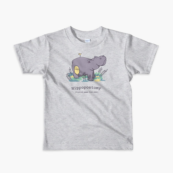 A Hippo or Hippopotamus with an ostomy bag — also known as a Hippopostomy. He is standing in some foliage smiling and has a bird on his back on a grey youth t-shirt.