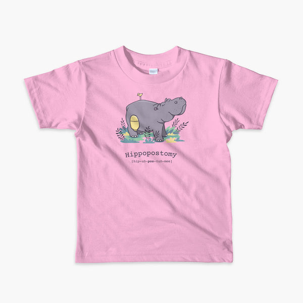 A Hippo or Hippopotamus with an ostomy bag — also known as a Hippopostomy. He is standing in some foliage smiling and has a bird on his back on a pink youth t-shirt.