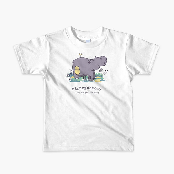 A Hippo or Hippopotamus with an ostomy bag — also known as a Hippopostomy. He is standing in some foliage smiling and has a bird on his back on a white youth t-shirt.