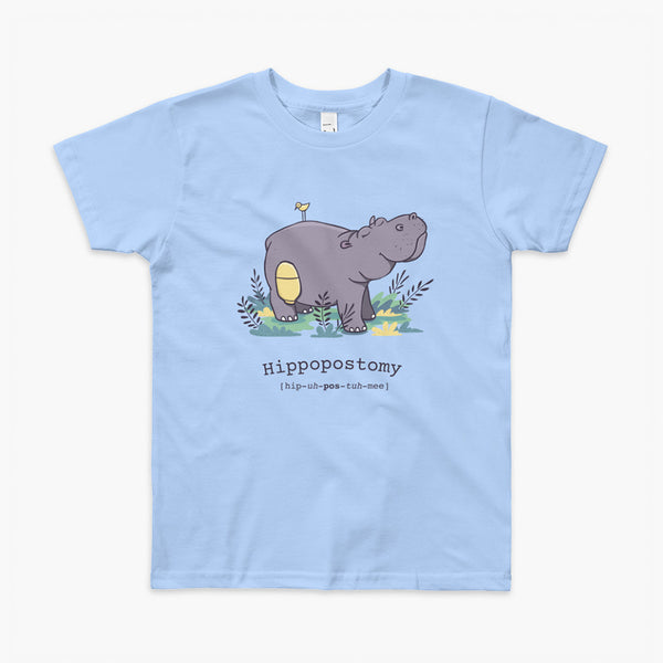 A Hippo or Hippopotamus with an ostomy bag — also known as a Hippopostomy. He is standing in some foliage smiling and has a bird on his back on a blue kids t-shirt.