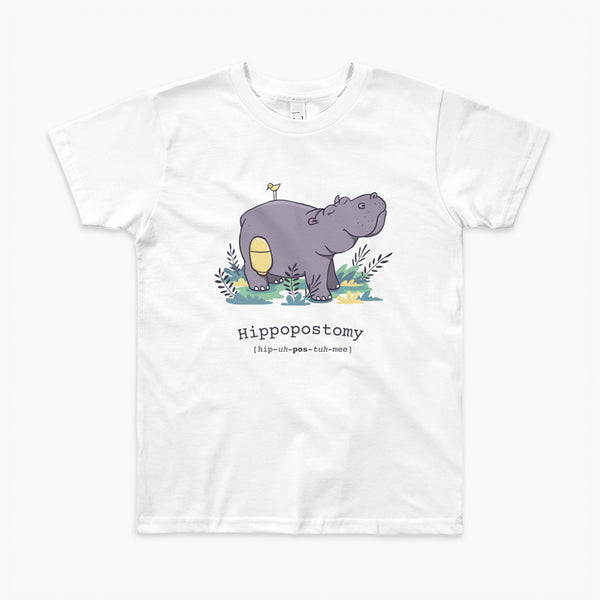 A Hippo or Hippopotamus with an ostomy bag — also known as a Hippopostomy. He is standing in some foliage smiling and has a bird on his back on a white kids t-shirt.