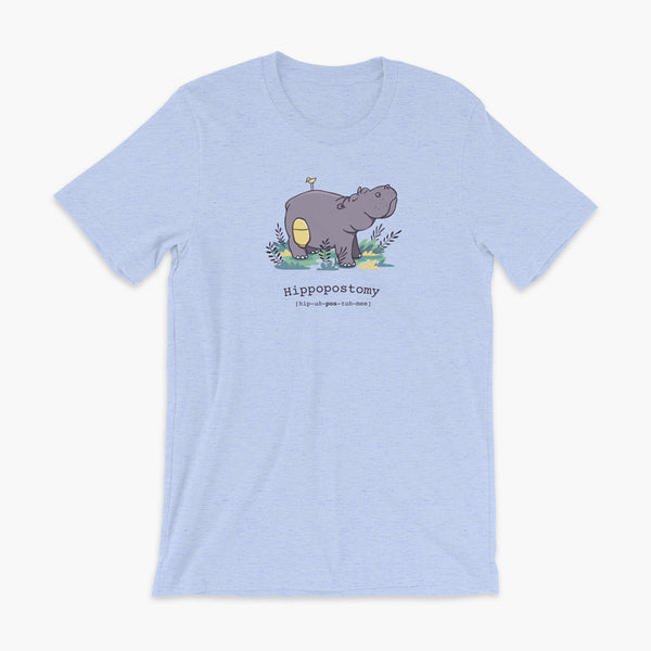 A Hippo or Hippopotamus with an ostomy bag — also known as a Hippopostomy. He is standing in some foliage smiling and has a bird on his back on a heather blue adult t-shirt.