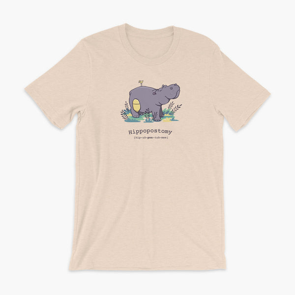 A Hippo or Hippopotamus with an ostomy bag — also known as a Hippopostomy. He is standing in some foliage smiling and has a bird on his back on a heather dust adult t-shirt.