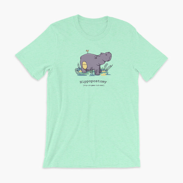 A Hippo or Hippopotamus with an ostomy bag — also known as a Hippopostomy. He is standing in some foliage smiling and has a bird on his back on a heather mint adult t-shirt.