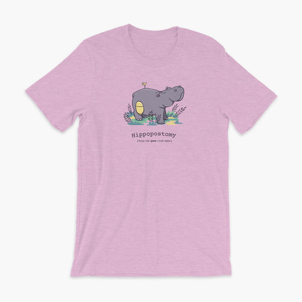 A Hippo or Hippopotamus with an ostomy bag — also known as a Hippopostomy. He is standing in some foliage smiling and has a bird on his back on a heather prism lilac adult t-shirt.