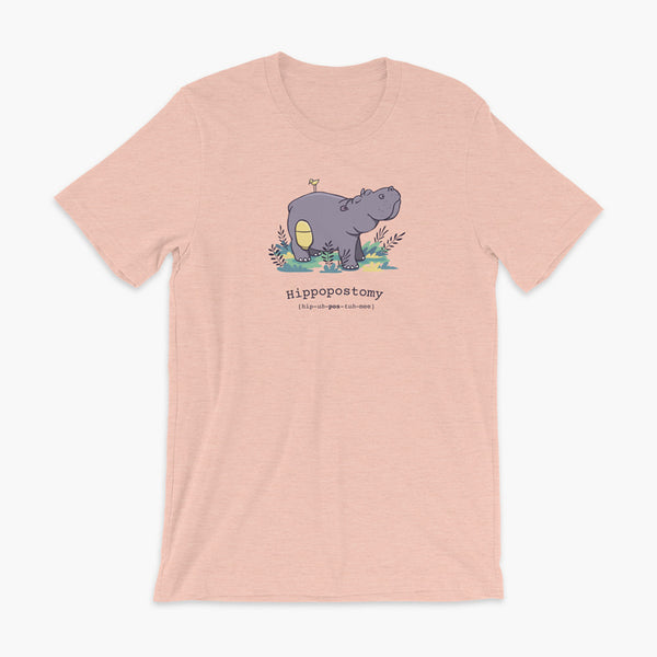 A Hippo or Hippopotamus with an ostomy bag — also known as a Hippopostomy. He is standing in some foliage smiling and has a bird on his back on a heather prism peach adult t-shirt.