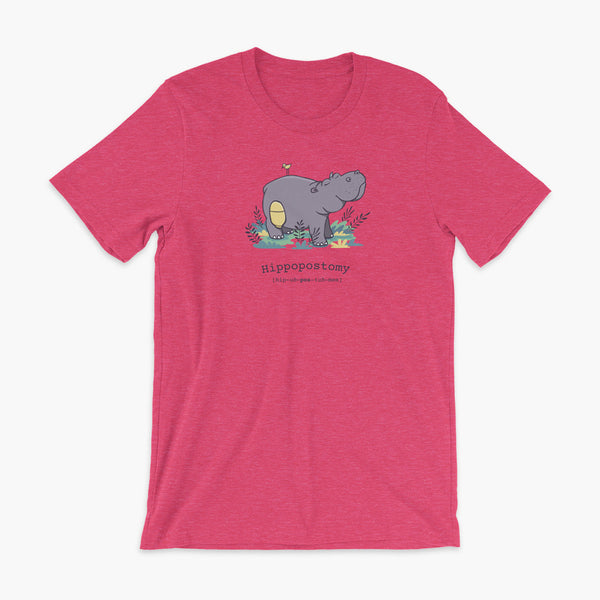 A Hippo or Hippopotamus with an ostomy bag — also known as a Hippopostomy. He is standing in some foliage smiling and has a bird on his back on a heather raspberry adult t-shirt.