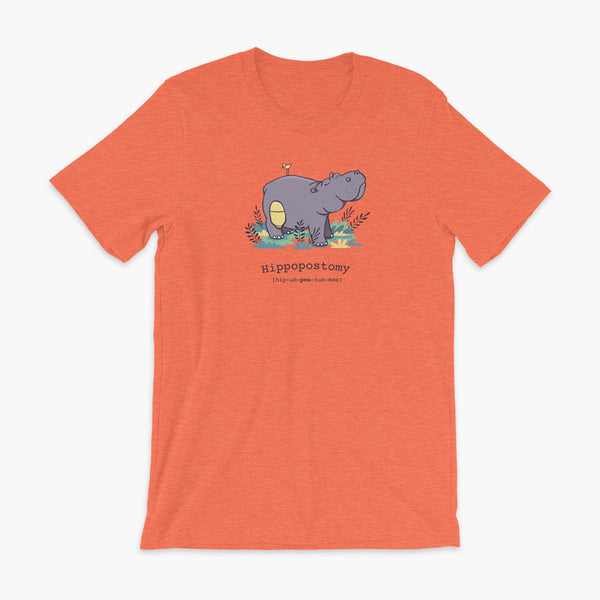 A Hippo or Hippopotamus with an ostomy bag — also known as a Hippopostomy. He is standing in some foliage smiling and has a bird on his back on a heather orange adult t-shirt.