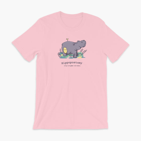 A Hippo or Hippopotamus with an ostomy bag — also known as a Hippopostomy. He is standing in some foliage smiling and has a bird on his back on a Pink adult t-shirt.