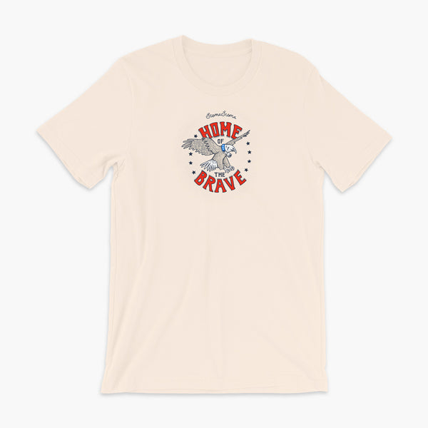 A patriotic American bald eagle with a trach or tracheostomy for the 4th of July and the words StomaStoma Home of the Brave and stars on a soft creme adult t-shirt