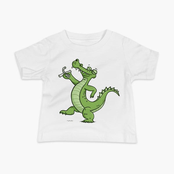 A green alligator or crocodile walks confidently with a big smile after bing decannulated of trach free. It is holding the trach in his hand. One a white infant t-shirt