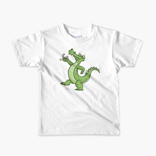 A green alligator or crocodile walks confidently with a big smile after bing decannulated of trach free. It is holding the trach in his hand. One a white kids t-shirt