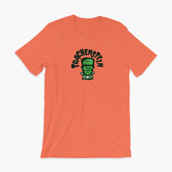 A Frankenstein with a trach or tracheostomy is called a Trachenstein! He has bolts in his neck and an HME on trach in his stoma. On a heather orange adult t-shirt