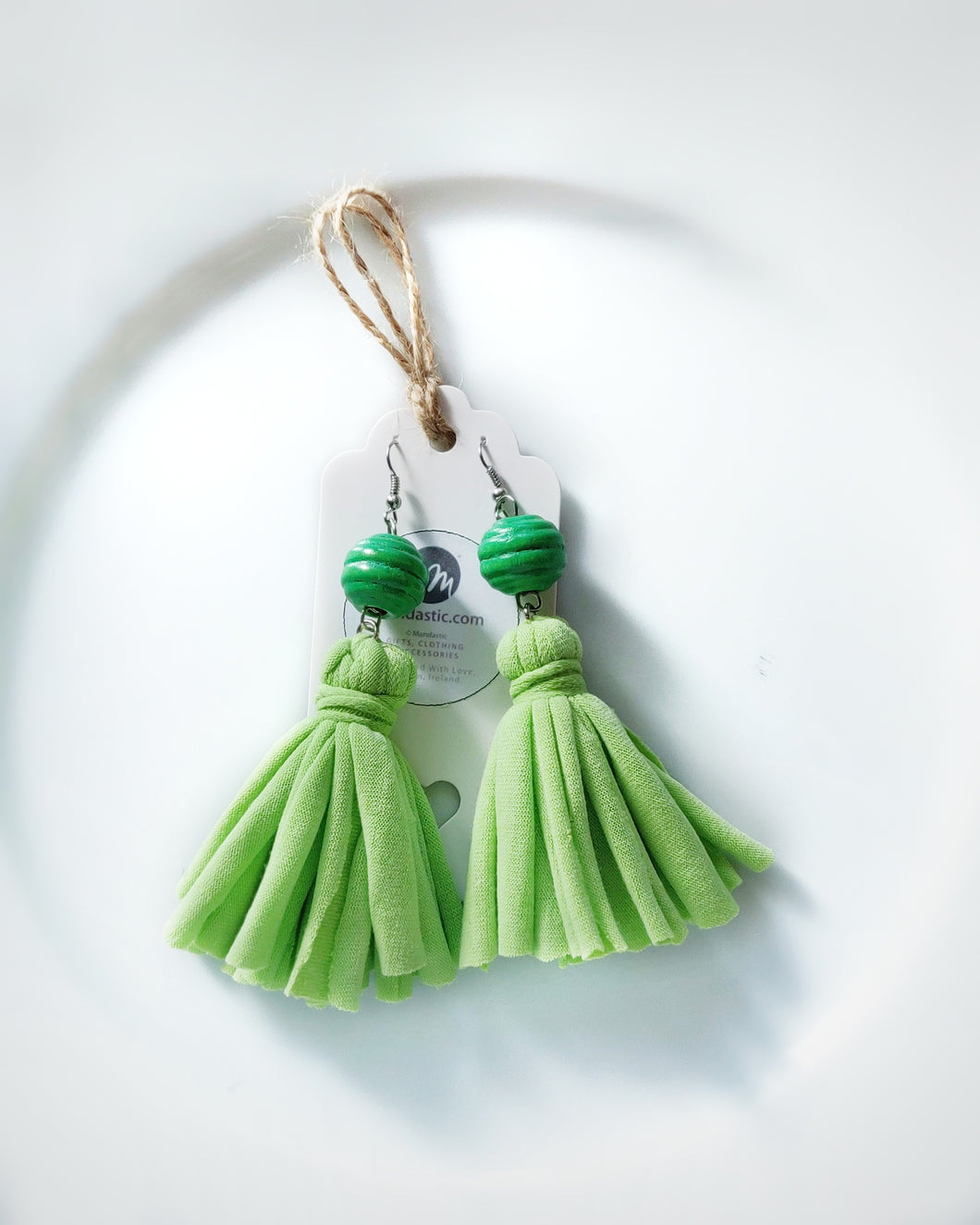 A pair of green tassel dangle earrings made with re-purposed cotton T-shirts and green wooden beads