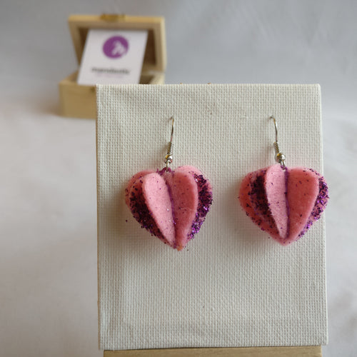 A pair of pink felt with purple glitter heart shaped dangle earrings