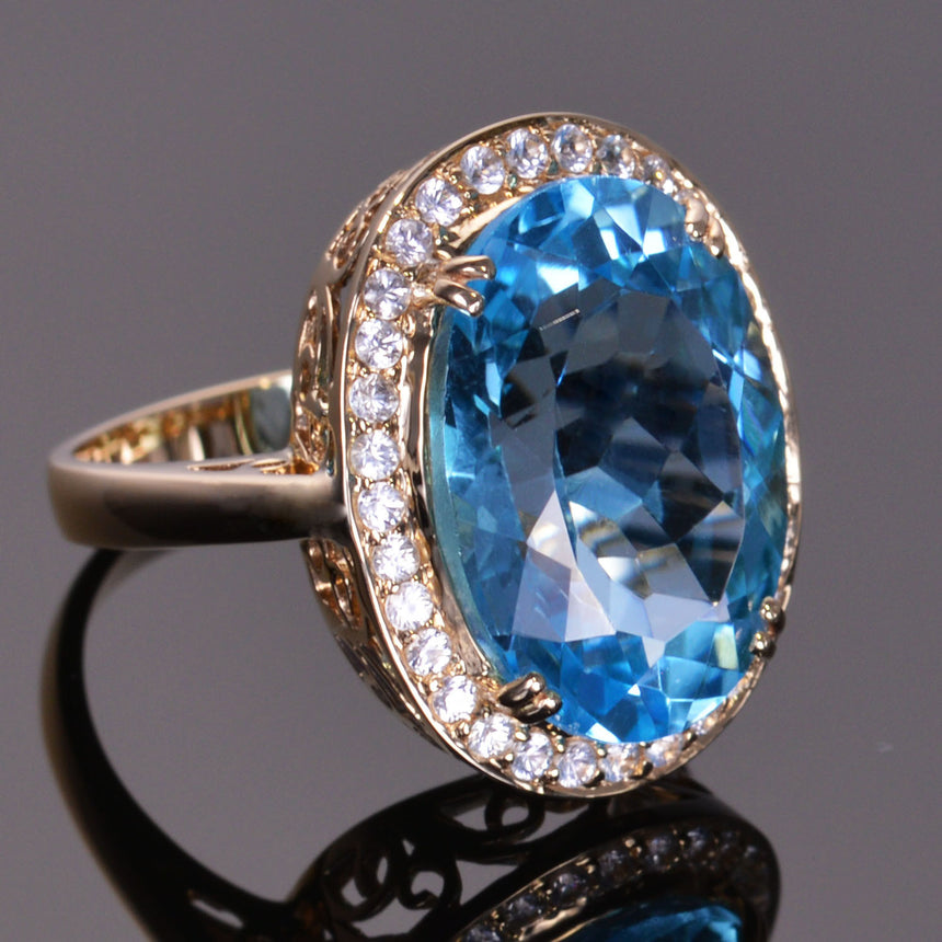 oval blue topaz ring with white sapphire halo in yellow gold