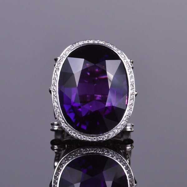 Oval amethyst ring with diamond halo, and diamond fluer de lis on each side of band in white gold.