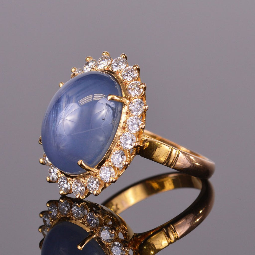 Cabochon star sapphire ring with diamond halo
