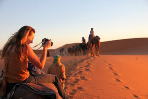 Tourist taking pictures at dusk over Moroccan sand dunes while riding a camel.