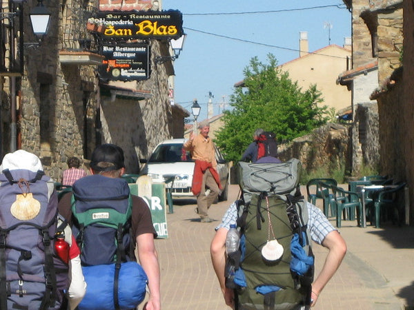 Backpackers visiting a town in their way to the Road of Santiago.