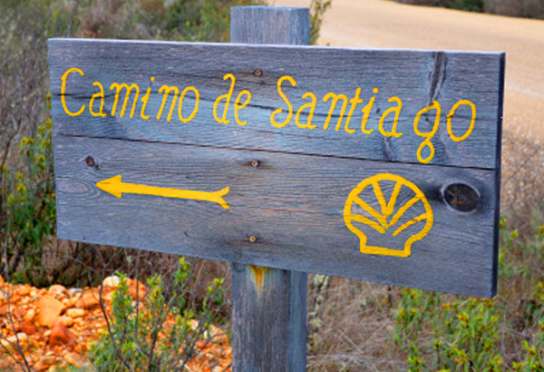 "A wooden sign with ""Camino de Santiago"" written in it"