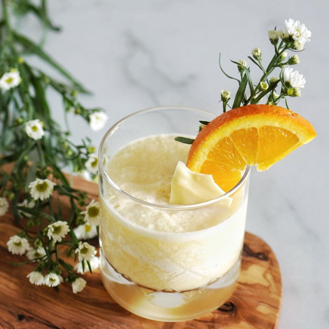 A tumbler of keto orange julius with a wedge of orange and some white flowers