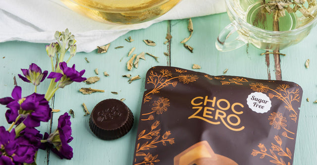 Bag of ChocZero PB Cups on a green wooden table with flowers and loose leaf tea scattered.