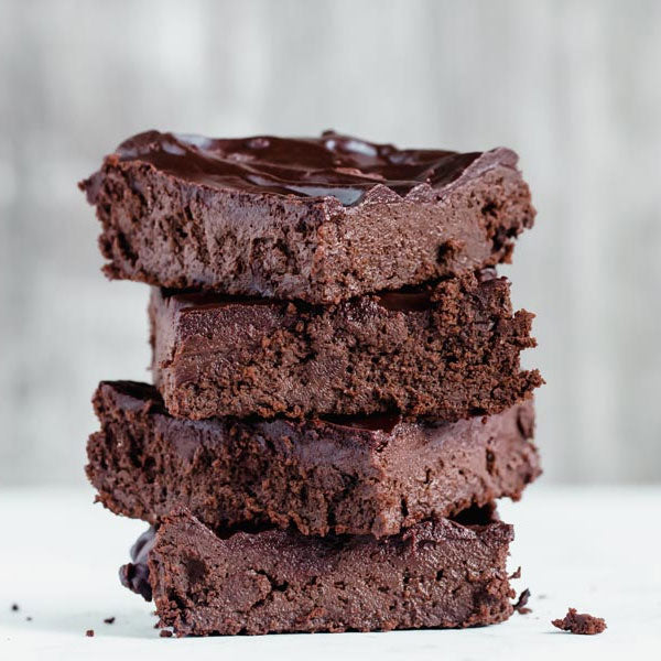 A stack of chocolate keto brownies piled up on top of each other