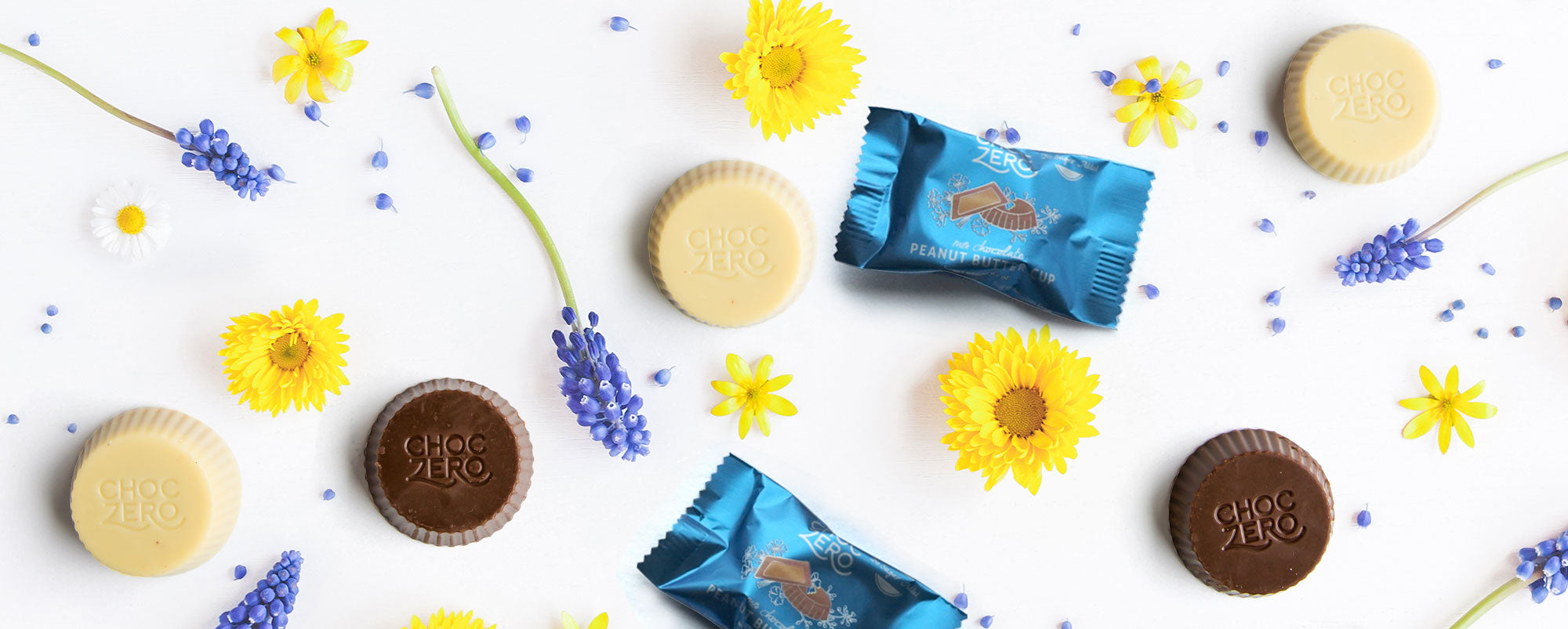 White and milk sugar free peanut butter cups scattered across a white background with blue and yellow flowers