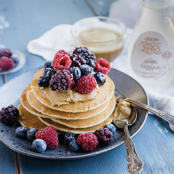 A stack of keto pancakes, topped with berries and drizzled with sugar free vanilla syrup